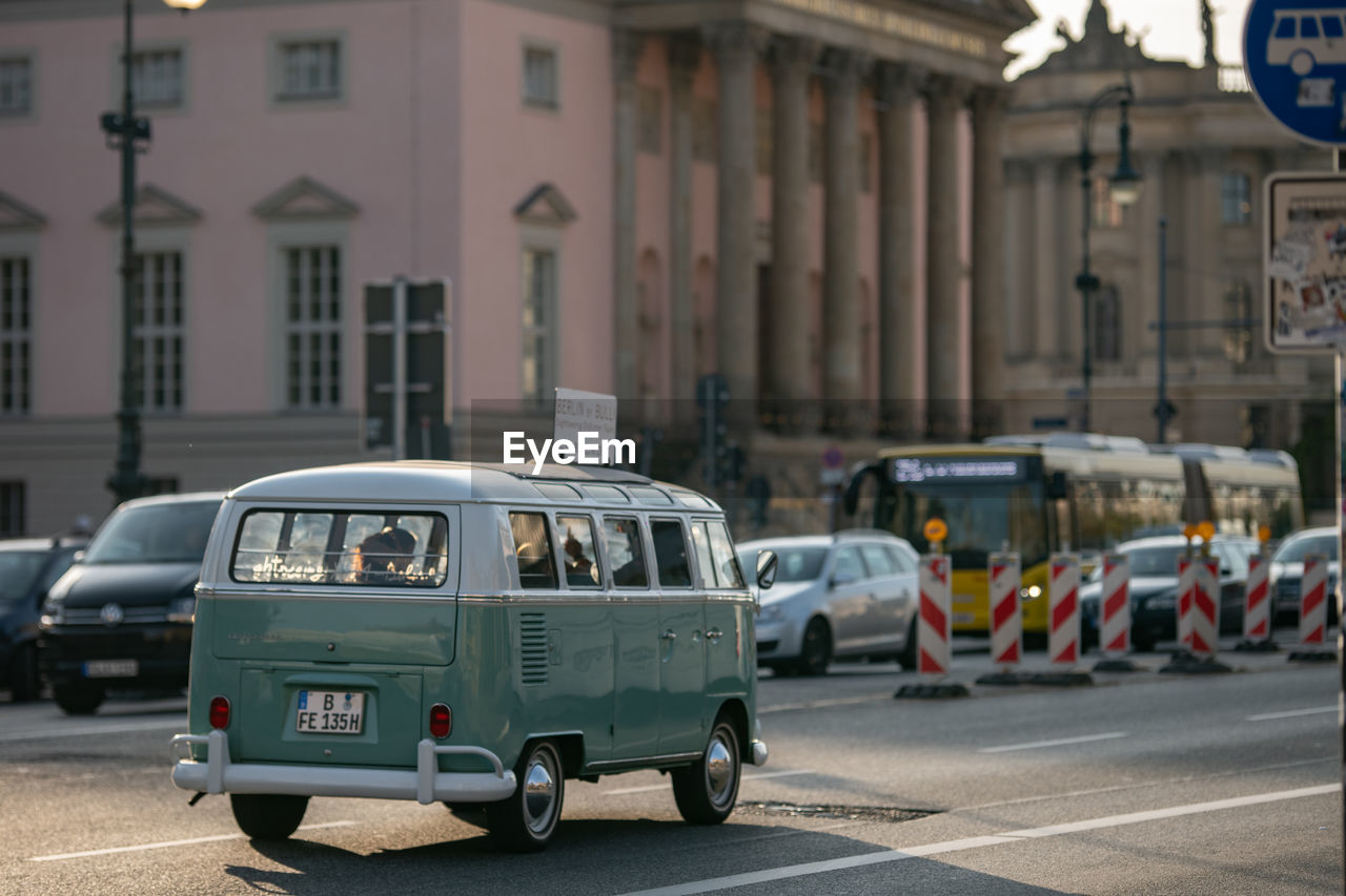 city, mode of transportation, car, transportation, architecture, street, building exterior, motor vehicle, built structure, land vehicle, focus on foreground, day, road, incidental people, city life, building, city street, outdoors, traffic, residential district