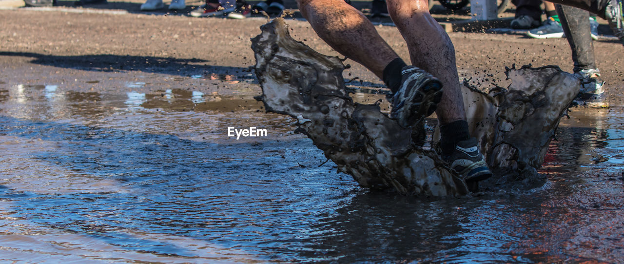 water, one person, low section, day, human body part, real people, human leg, nature, body part, men, outdoors, shoe, lifestyles, waterfront, wet, sport, occupation, motion, human limb, mud, human foot