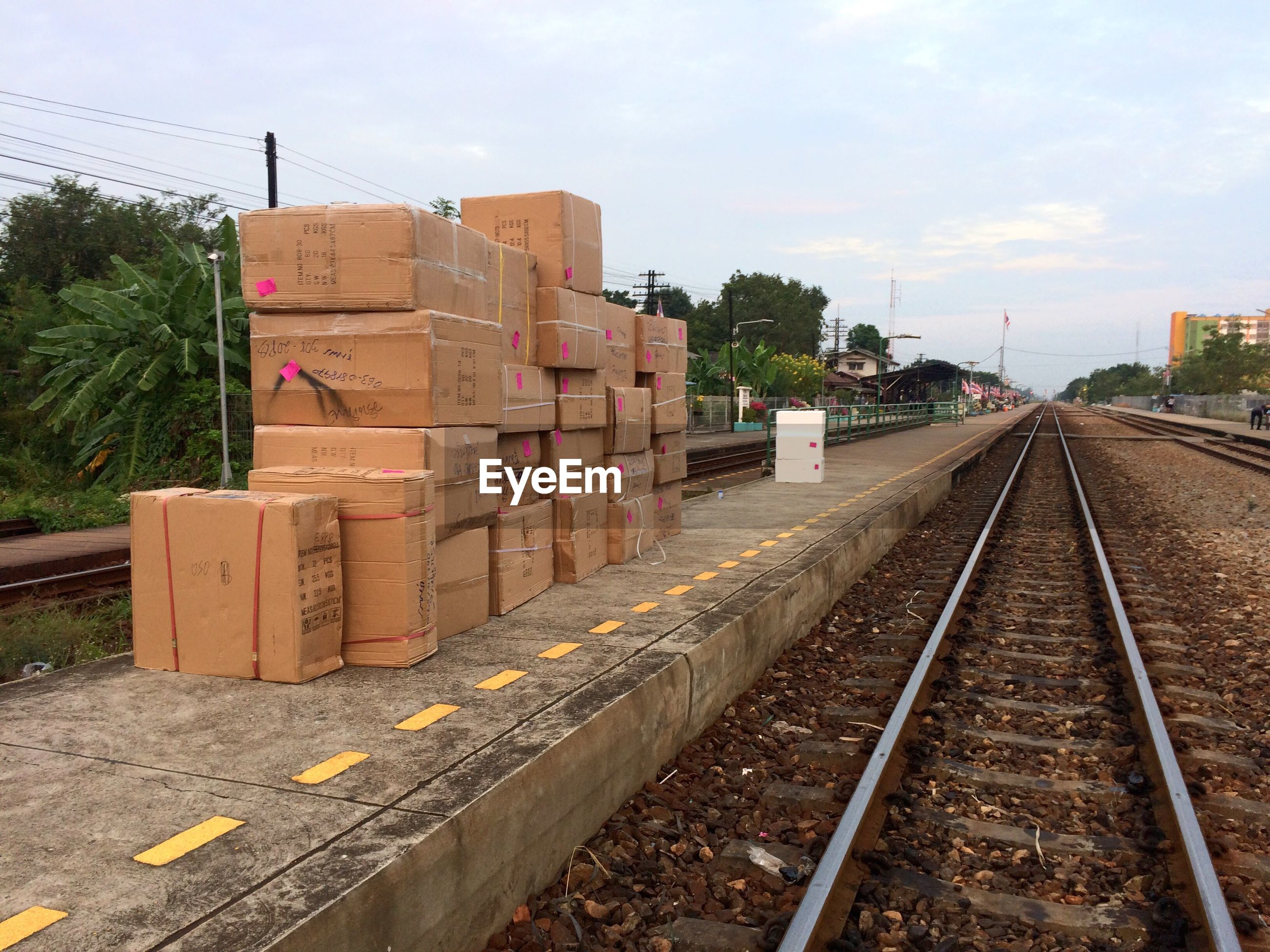 Stacked boxes on railroad station platform against sky