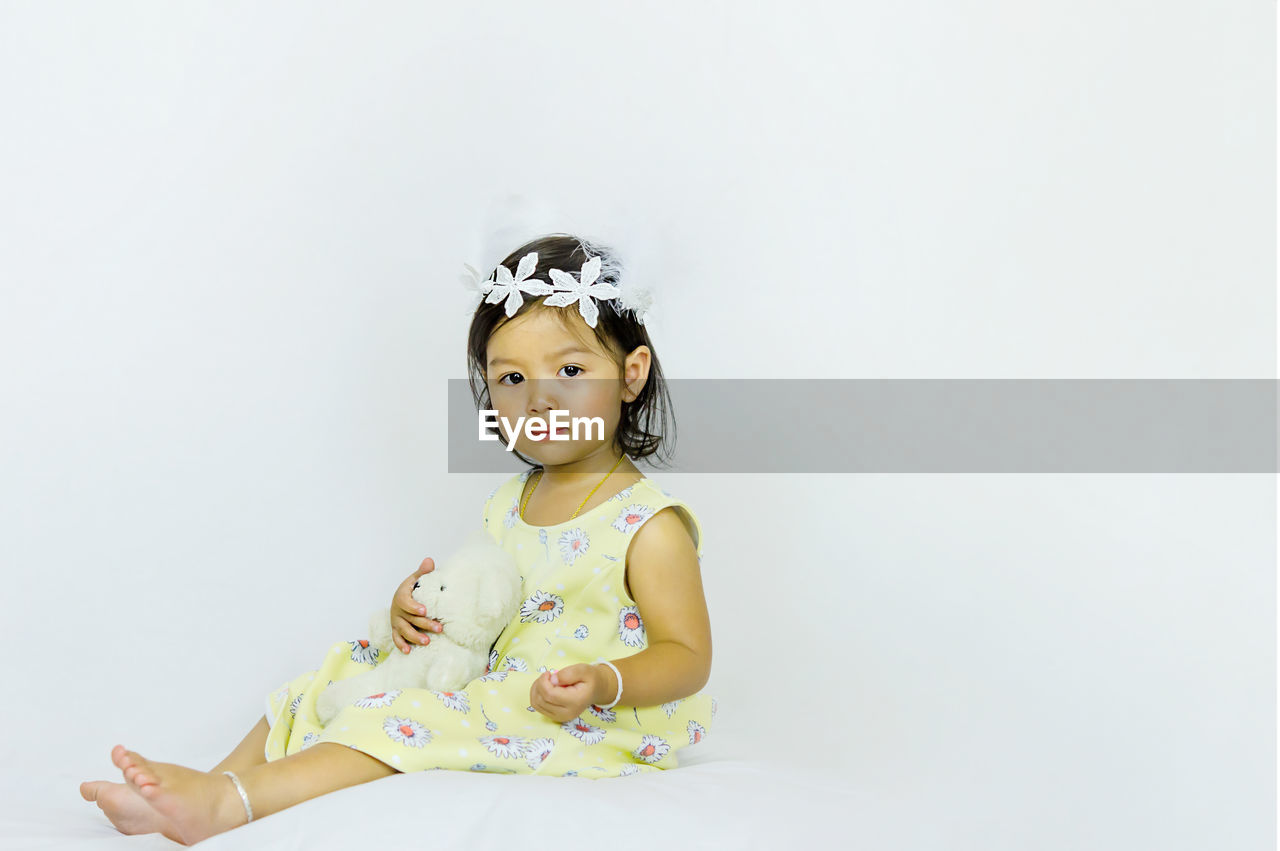 Portrait of cute girl sitting against white background