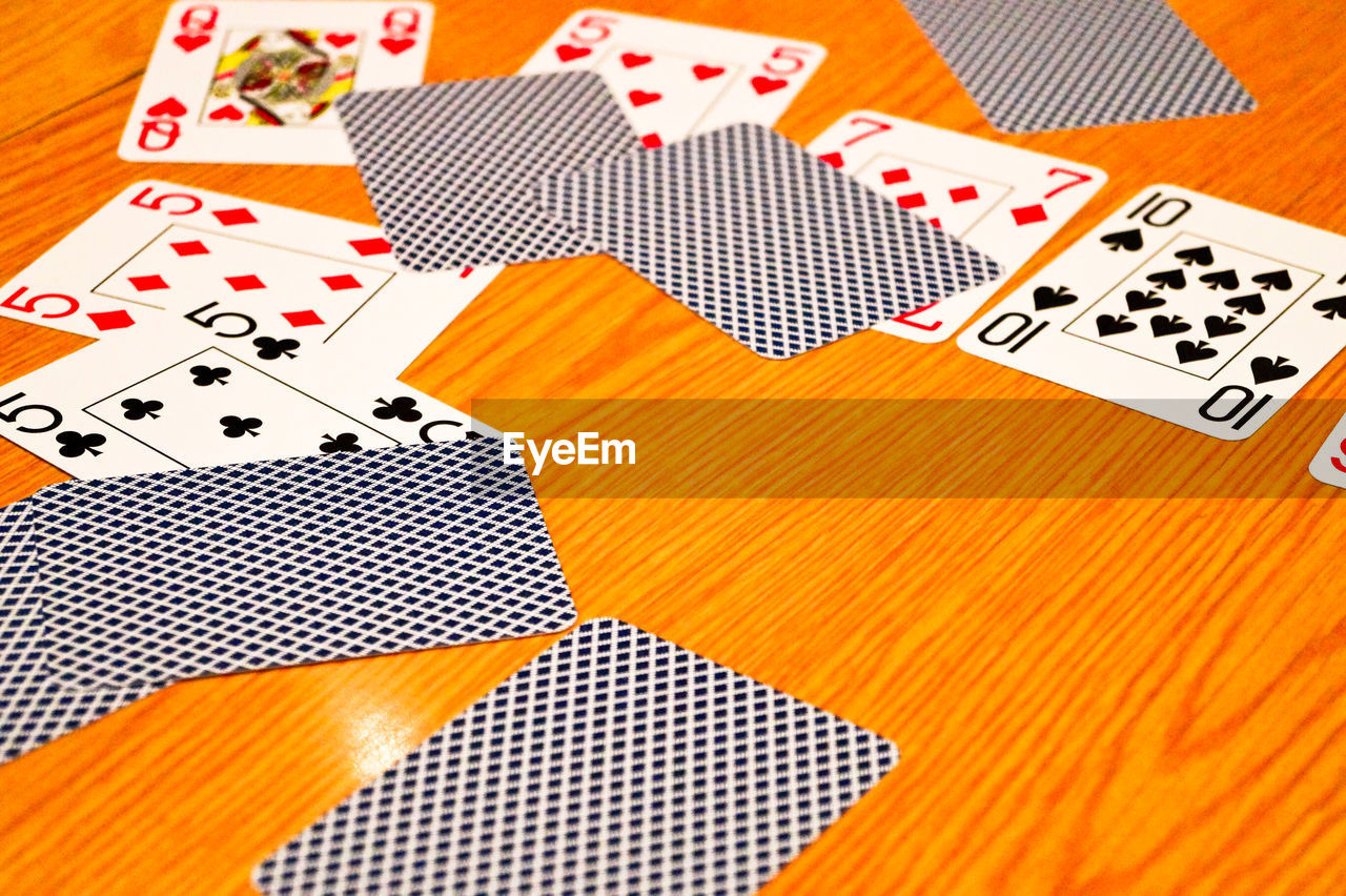 High angle view of cards on brown table