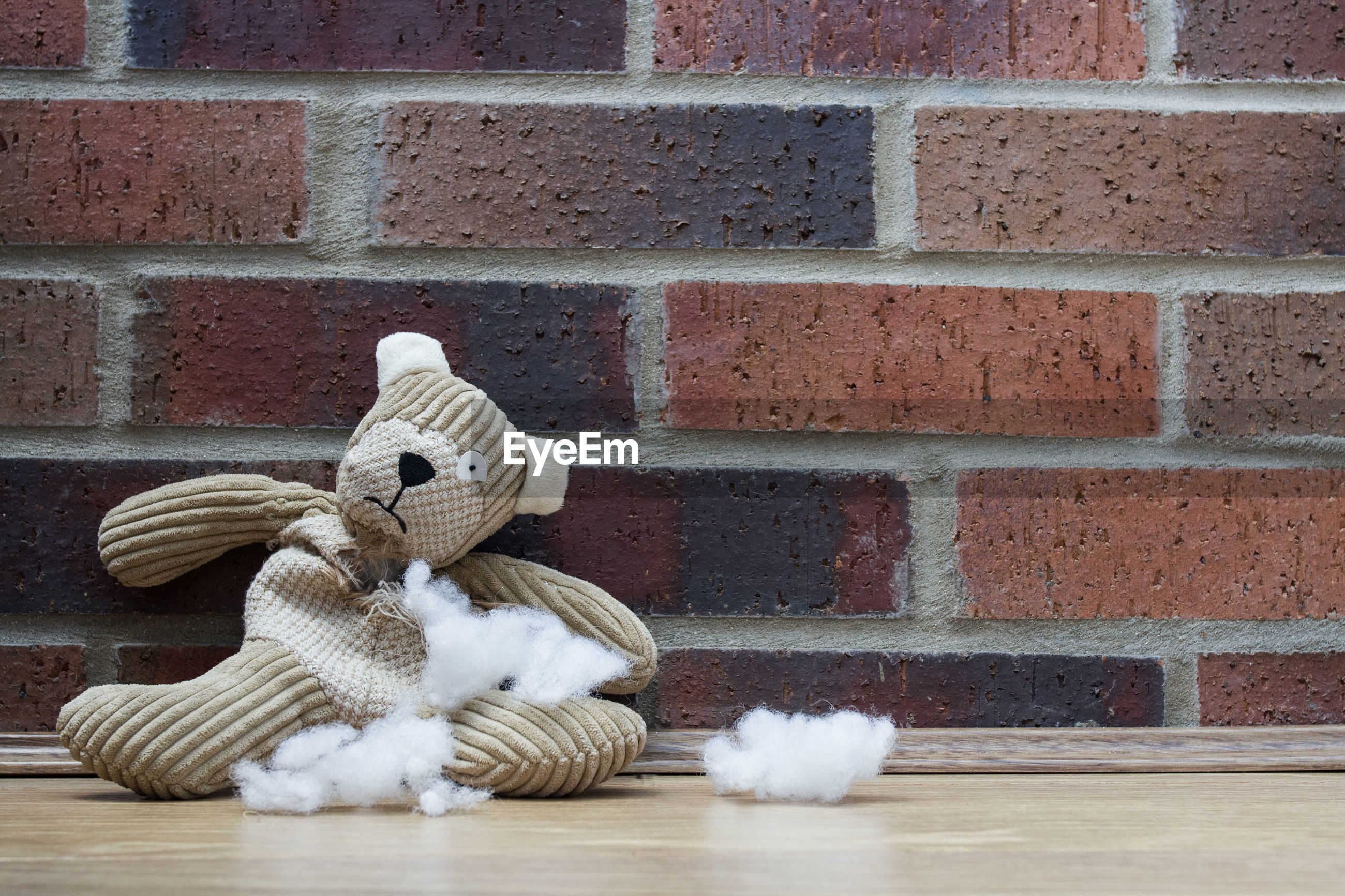 Close-up of torn stuffed toy on wooden table by brick wall