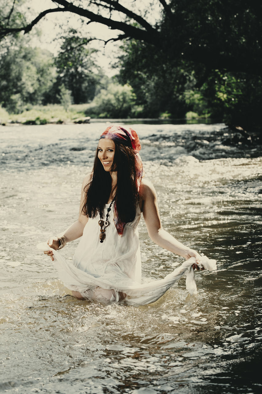 Smiling Woman Standing In River At Forest