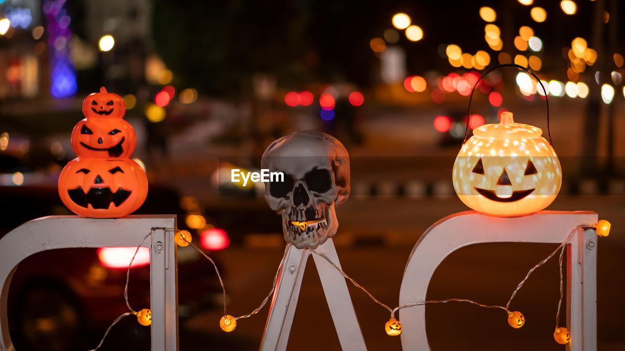 Close-up of skull and jack o lanterns with illuminated lighting at night