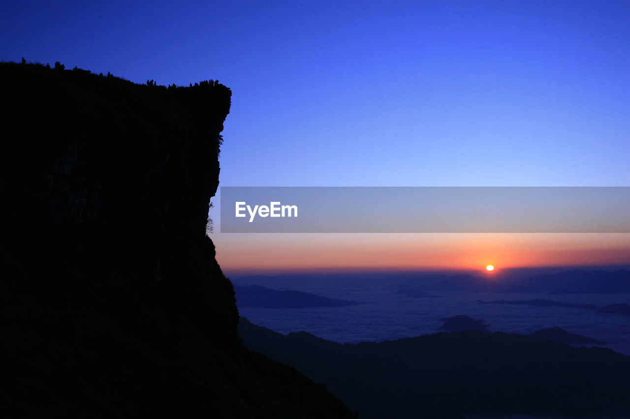 sky, beauty in nature, silhouette, mountain, sunset, tranquil scene, scenics - nature, tranquility, nature, idyllic, non-urban scene, clear sky, no people, rock, copy space, blue, mountain range, sea, outdoors, mountain peak