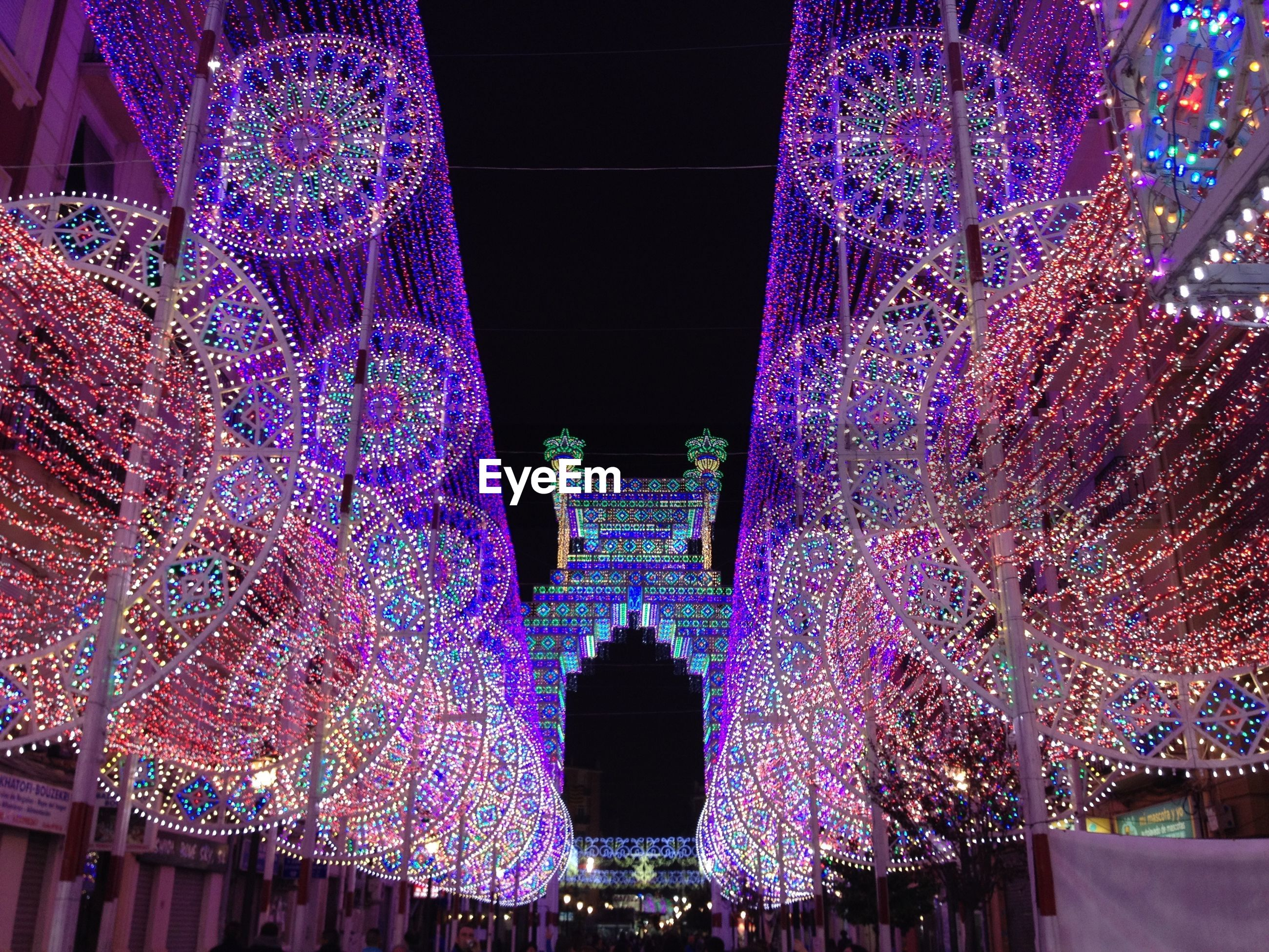 Low angle view of illuminated colorful lighting decorations in city at night