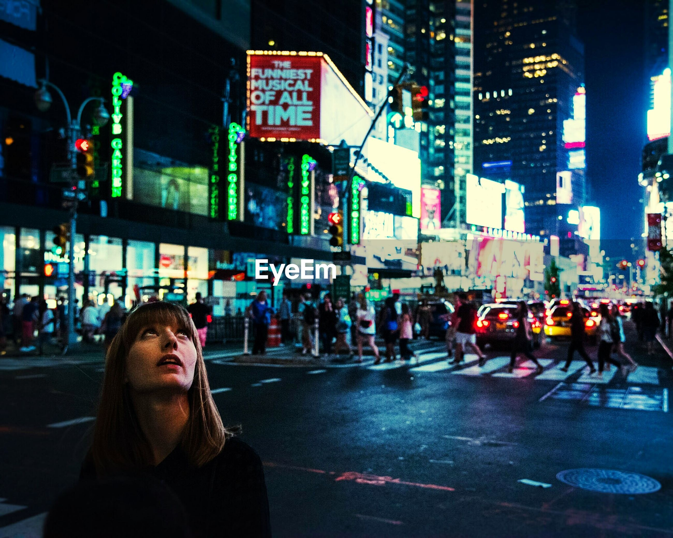 Close-up of young woman looking up while standing at times square during night