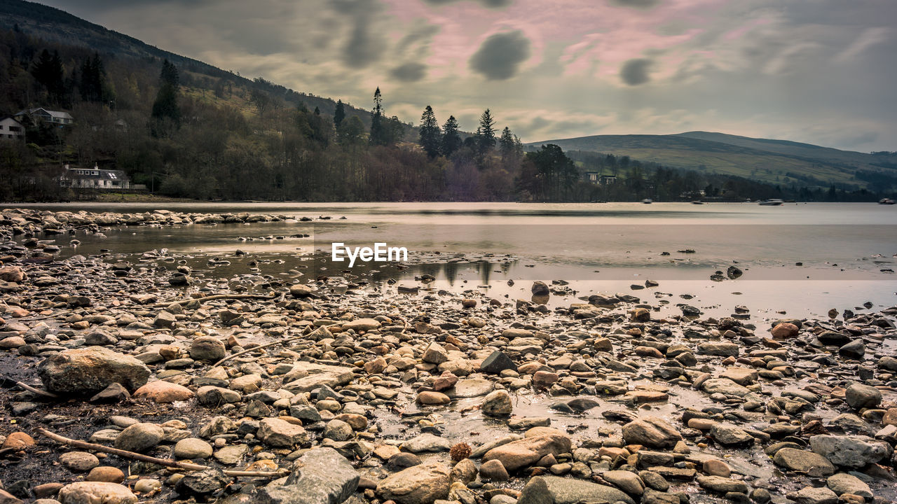 water, mountain, sky, beauty in nature, tranquil scene, cloud - sky, scenics - nature, tranquility, nature, rock, lake, tree, no people, day, non-urban scene, idyllic, solid, beach, reflection, outdoors, pebble