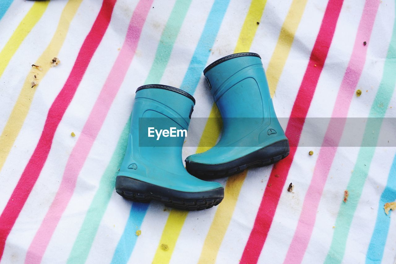 High angle view of rubber boots on multi colored sheet