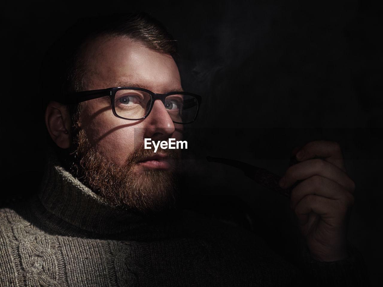 Portrait Of Mature Man Smoking While Sitting In Darkroom