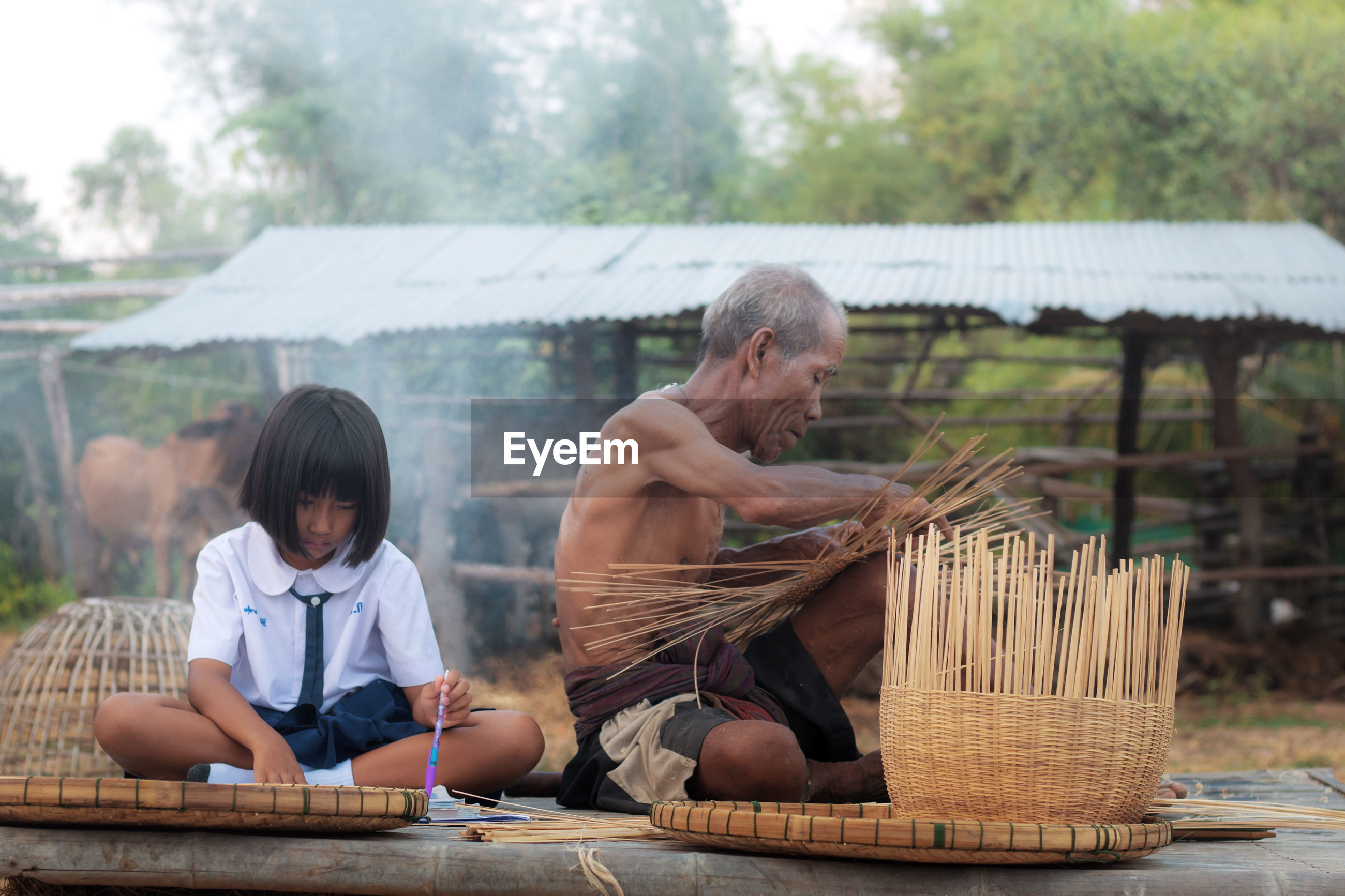 Grandfather by girl with basket on field