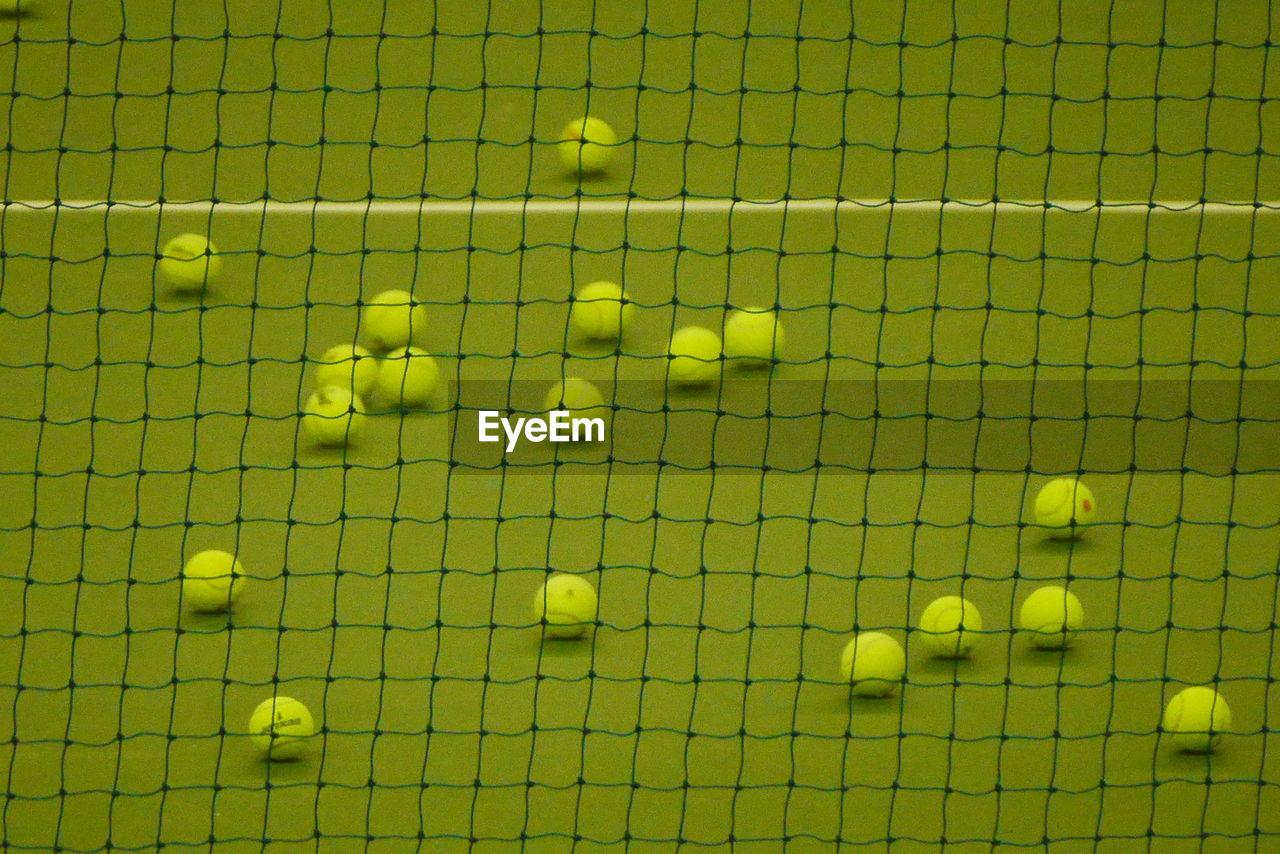 High angle view of tennis balls on court seen through net
