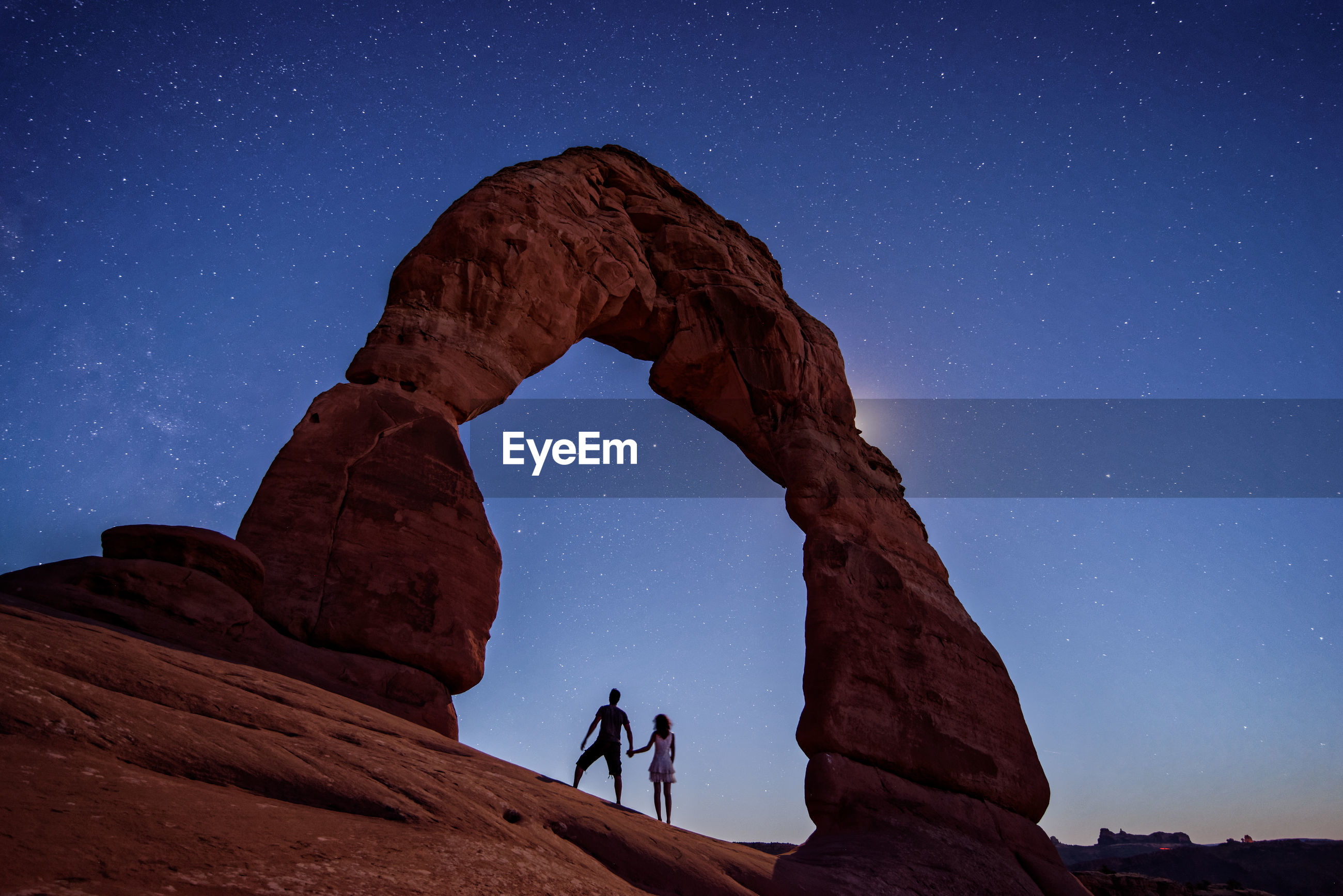 Low angle view of couple standing at arches national park during sunset