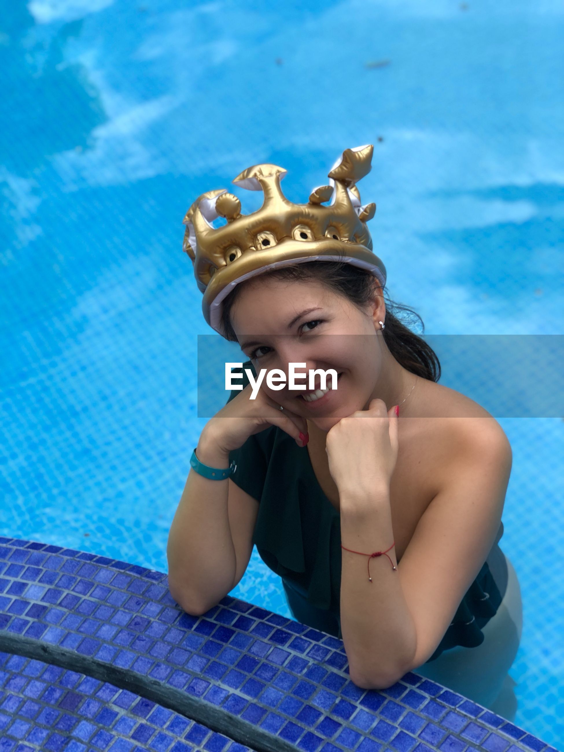 Portrait of smiling young woman wearing inflatable crown swimming pool