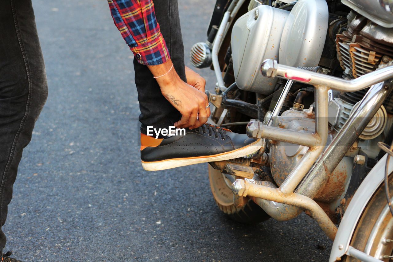 Low section of man tying shoelace on motorcycle