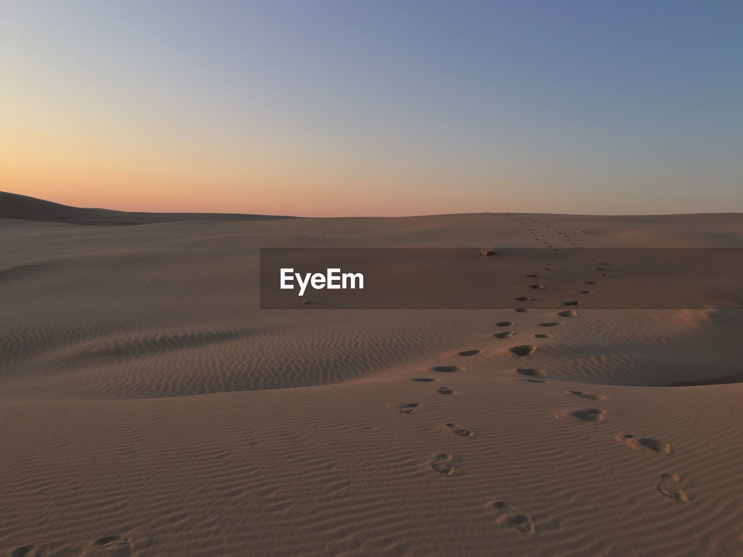 Footprints on sand dunes against clear sky during sunset at port stephens