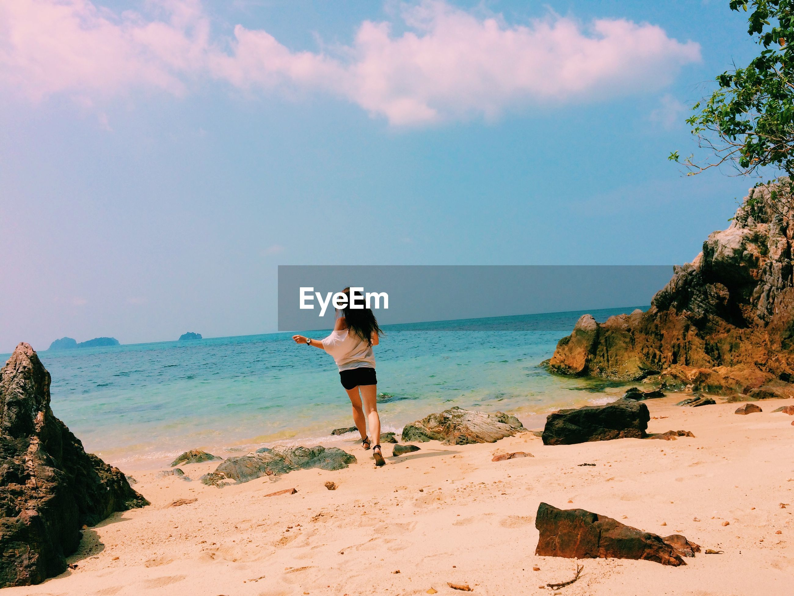 Rear view of woman running at beach against sky