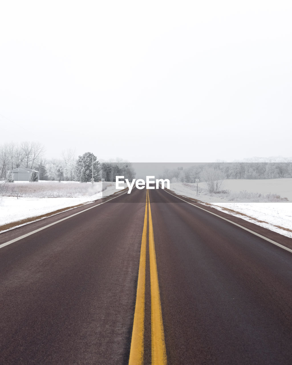ROAD LEADING TOWARDS SNOW COVERED LANDSCAPE