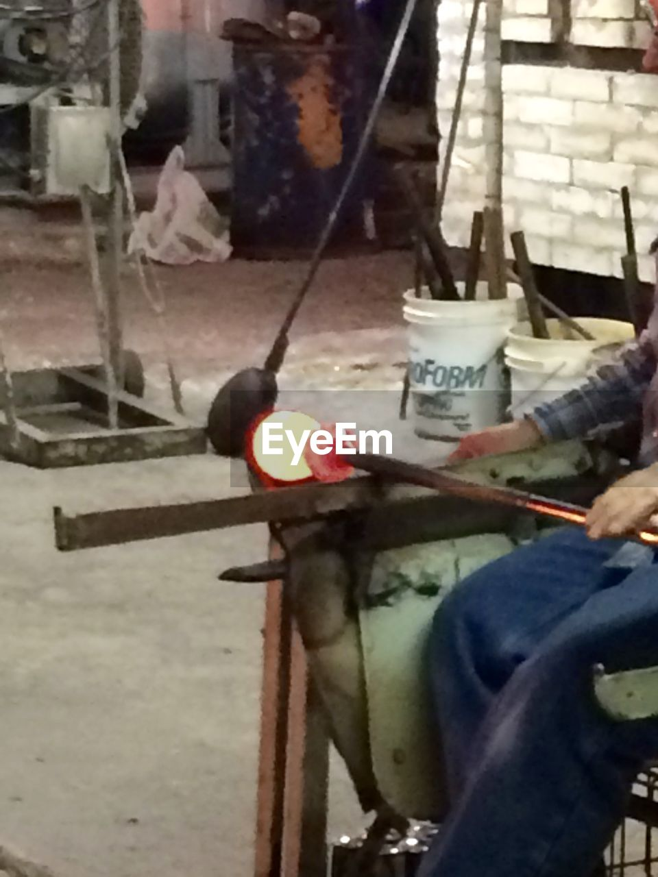 one person, real people, holding, human body part, human hand, heat - temperature, working, hand, men, occupation, skill, indoors, food and drink, low section, burning, workshop, sitting, fire, unrecognizable person, jeans, metal industry