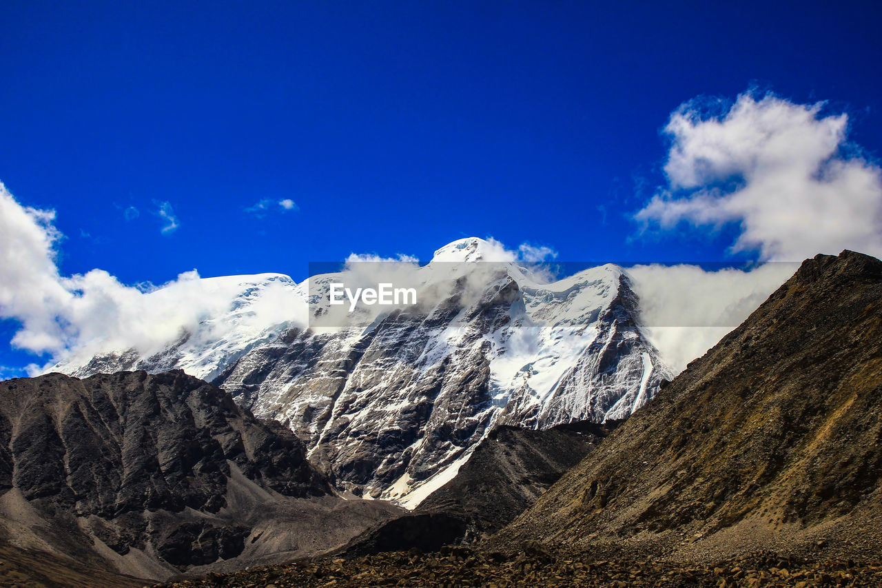 sky, mountain, scenics - nature, cloud - sky, beauty in nature, mountain range, tranquil scene, tranquility, landscape, environment, non-urban scene, blue, nature, idyllic, day, no people, remote, snow, cold temperature, physical geography, mountain peak, snowcapped mountain, outdoors, formation, mountain ridge, arid climate