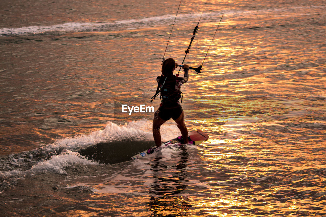 High angle view of man kiteboarding on sea during sunset