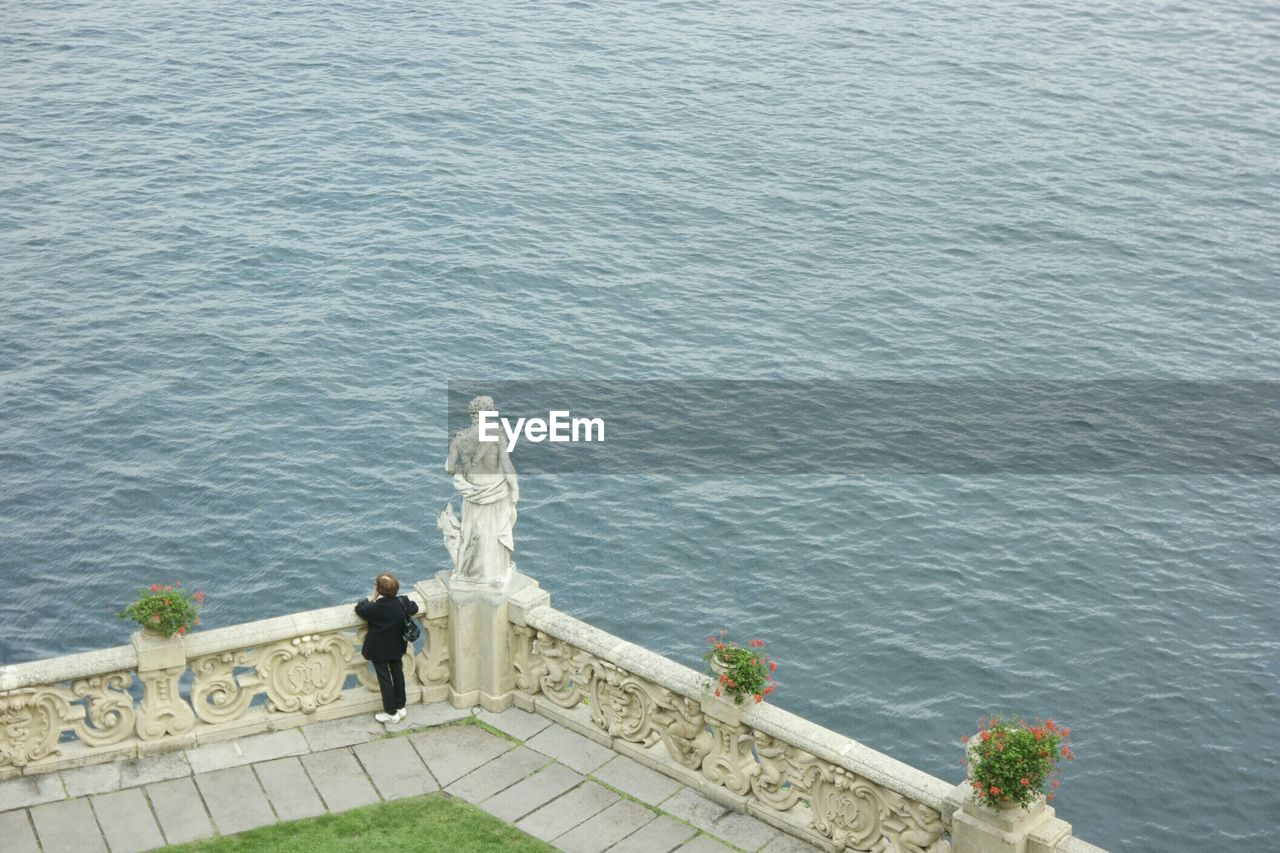 High angle view of woman standing at observation point by sea