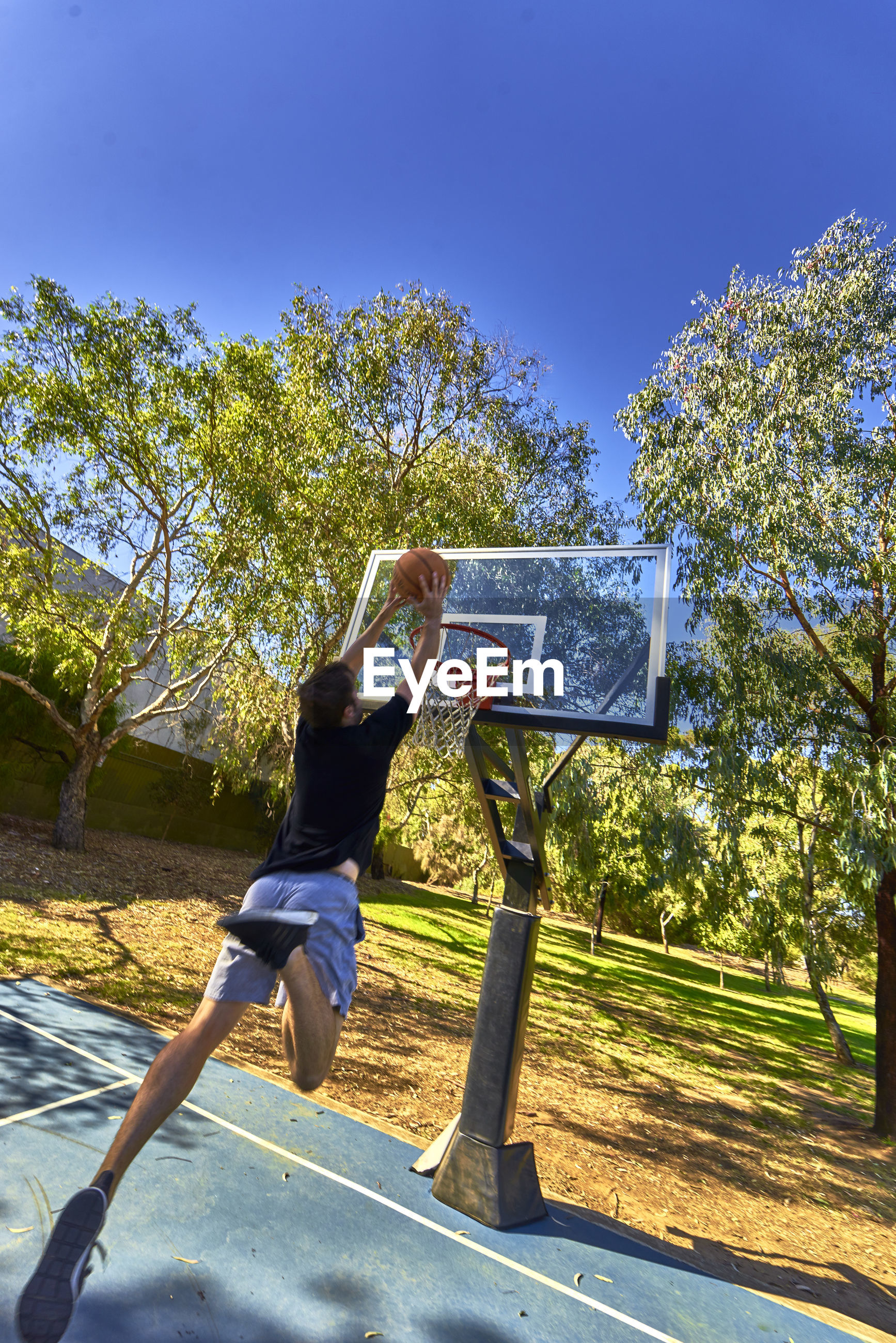 Rear view of man putting ball in basketball hoop against clear sky