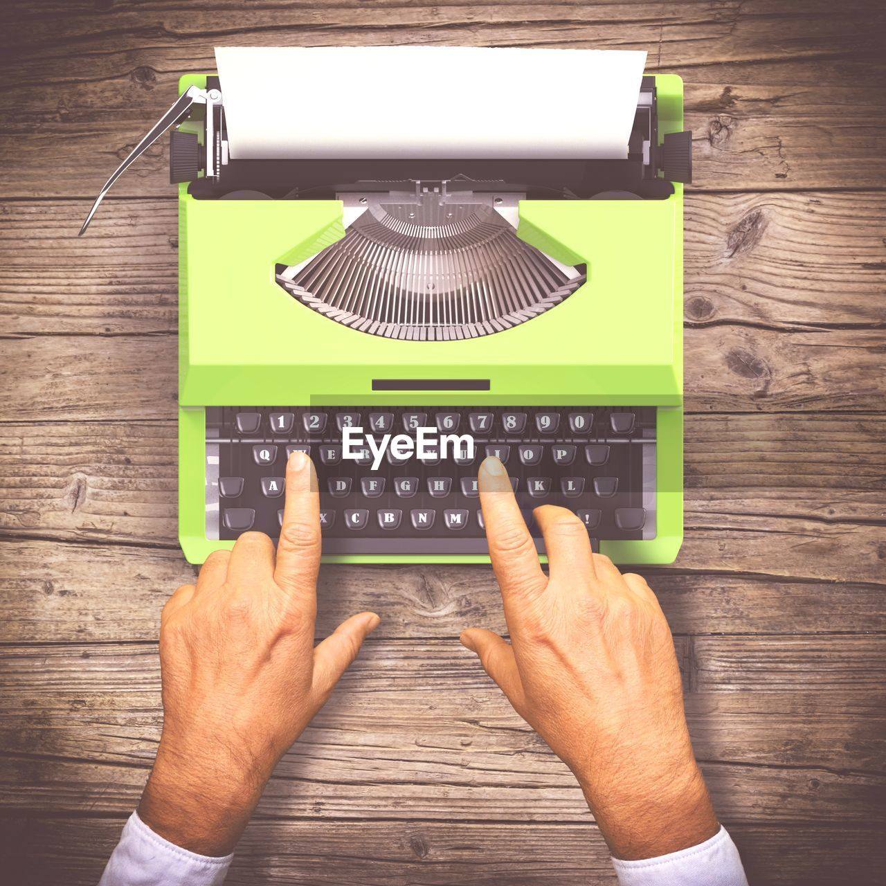 Cropped hands of man typing on typewriter at table