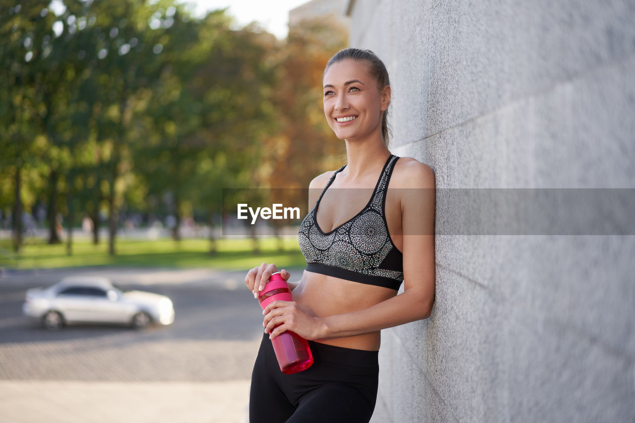 Smiling woman holding bottle standing against wall outdoor