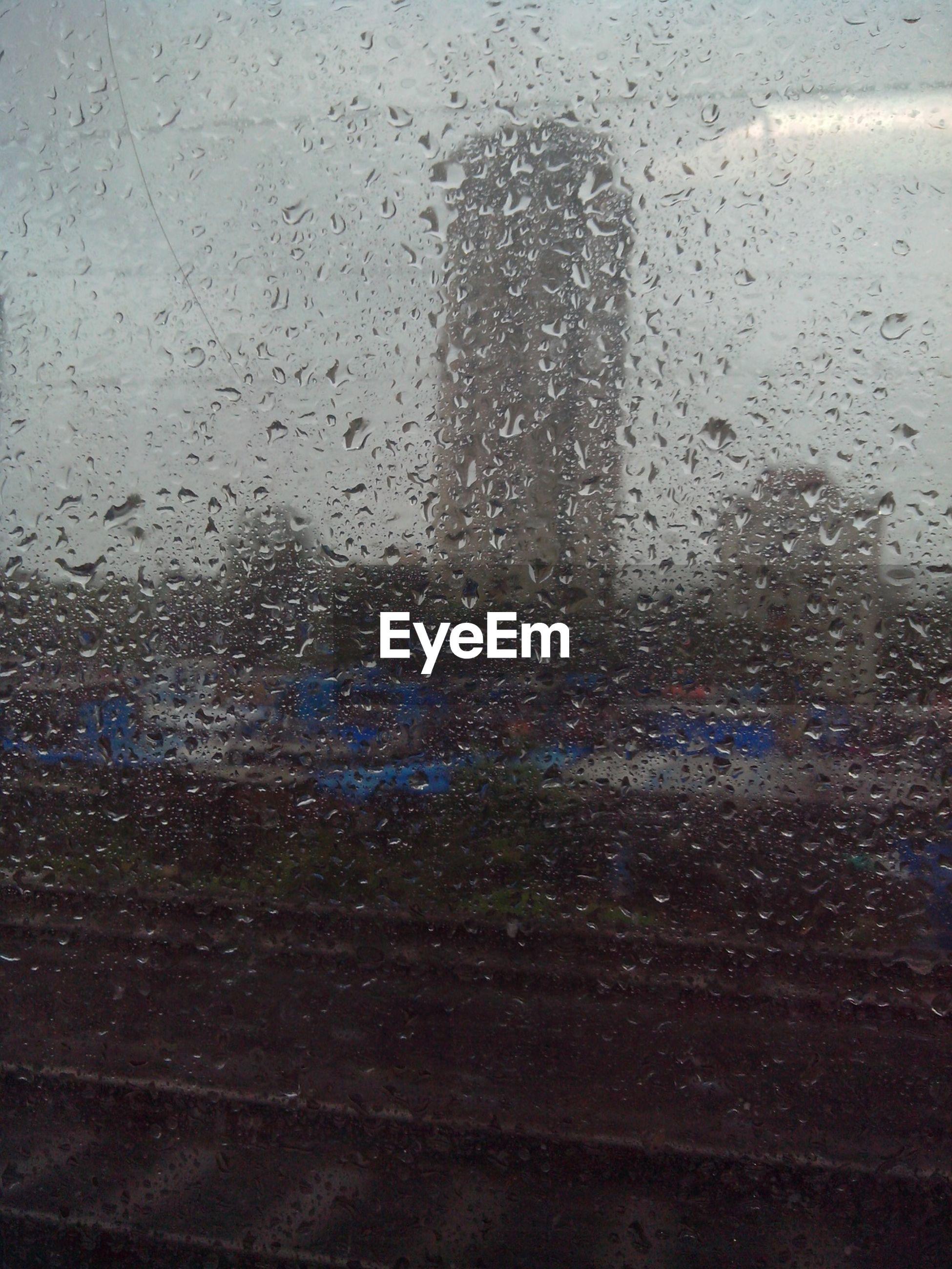 Waterdrops on glass against buildings