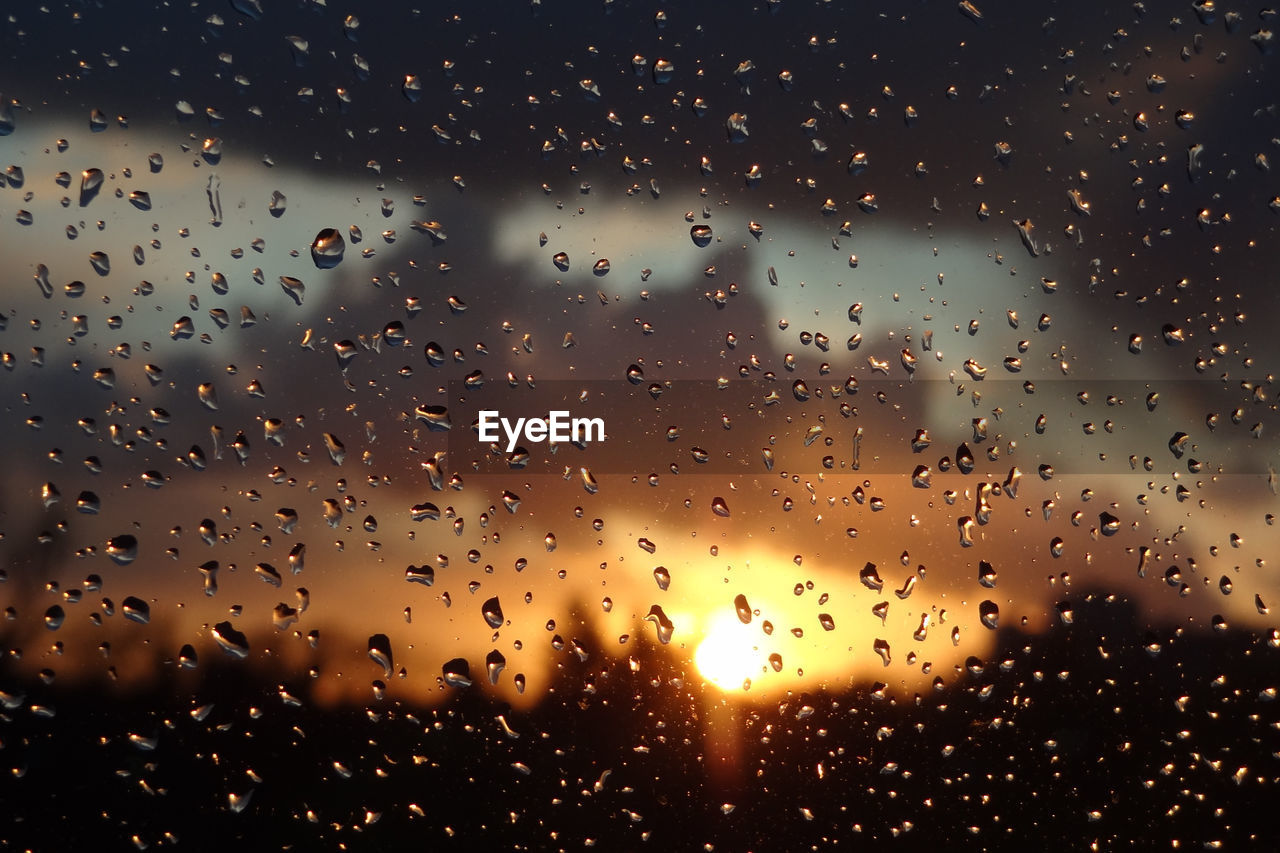Sky during sunset seen through wet glass window