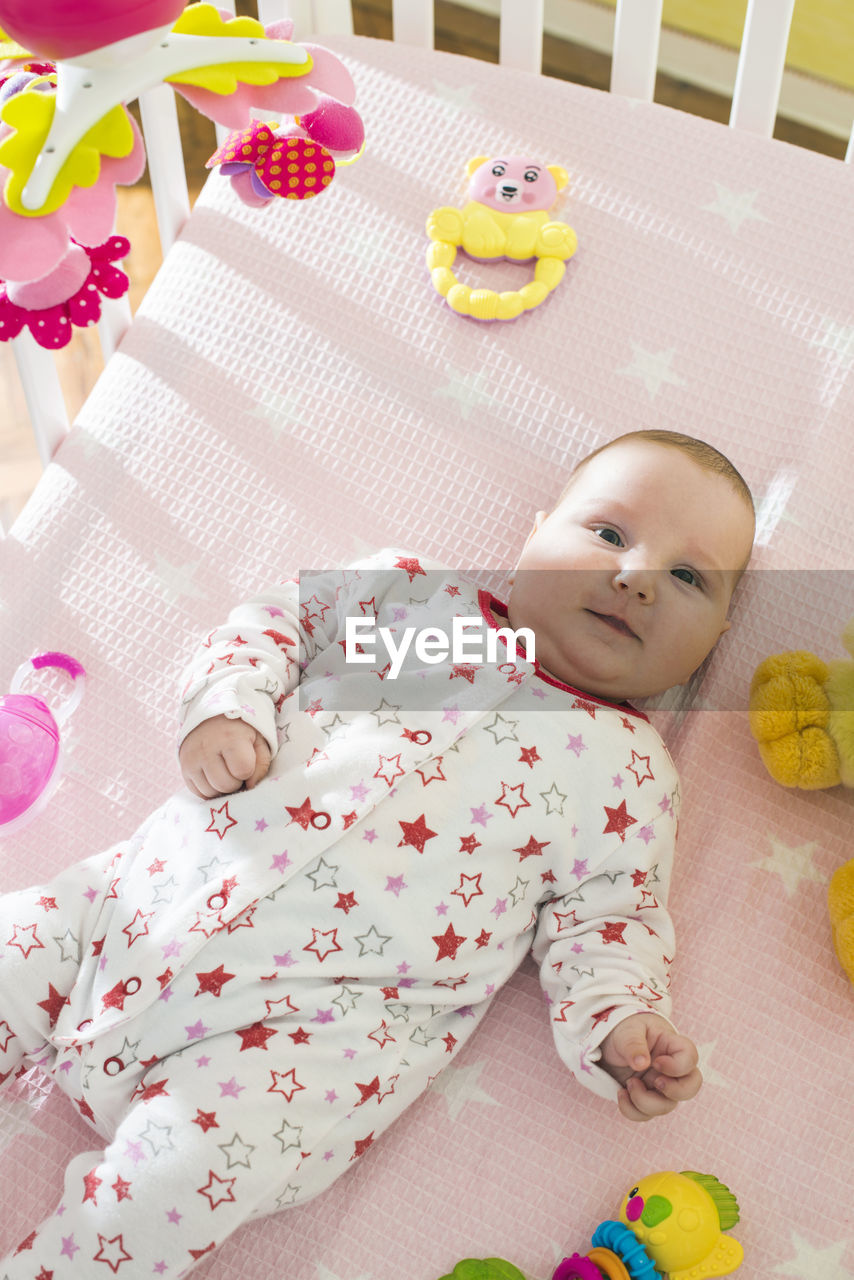 Portrait of baby girl with toys lying on crib at home