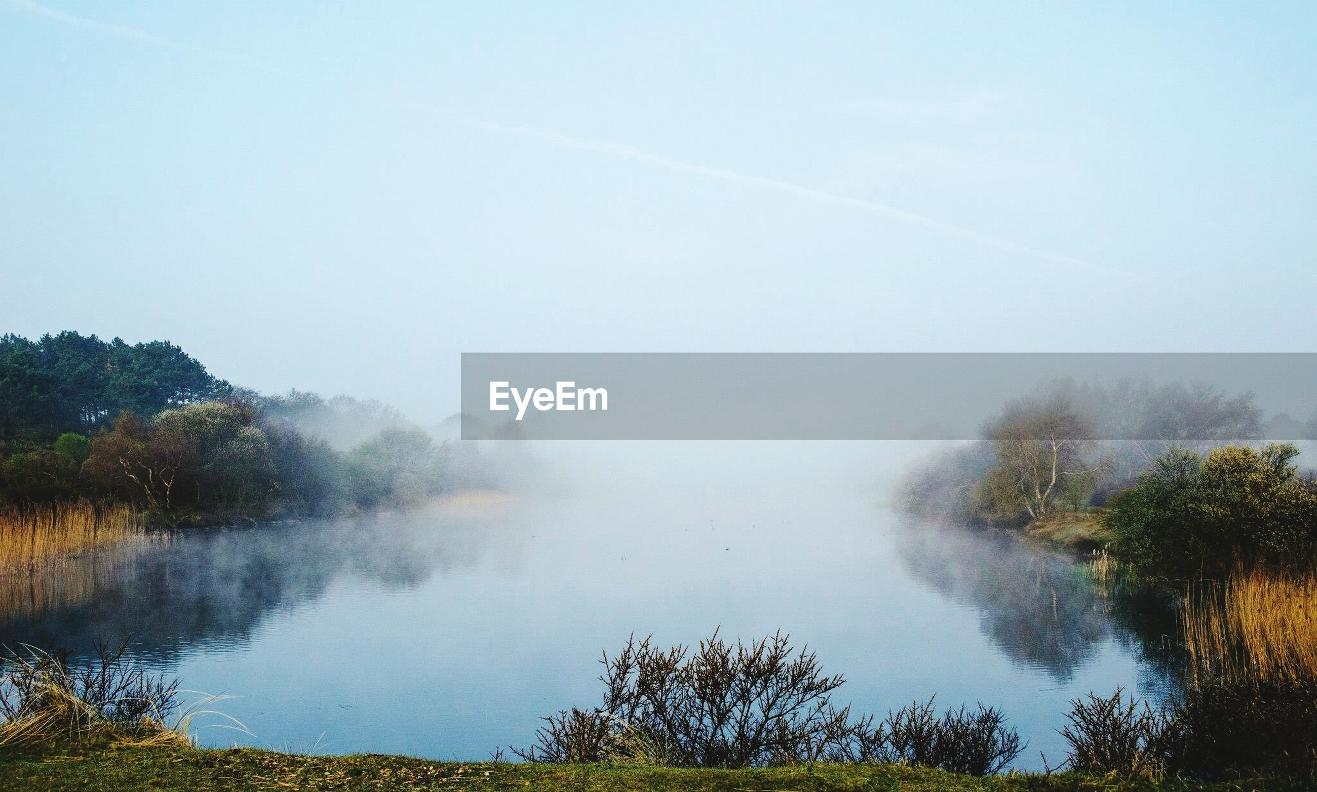scenics, beauty in nature, tranquil scene, water, tranquility, tree, fog, nature, mountain, lake, foggy, idyllic, non-urban scene, sky, landscape, weather, forest, tourism, copy space
