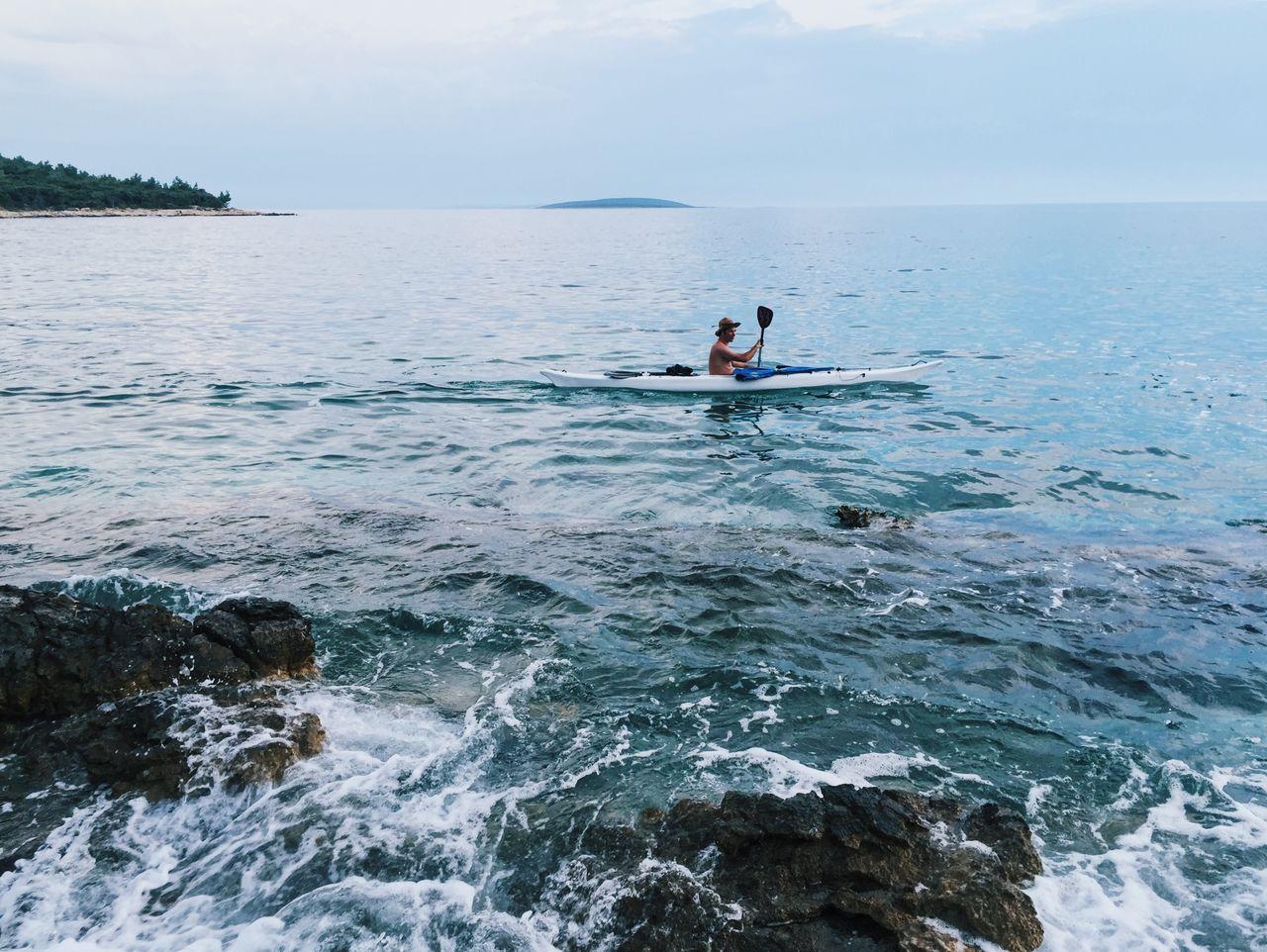 Man Paddling On Sea Against Sky