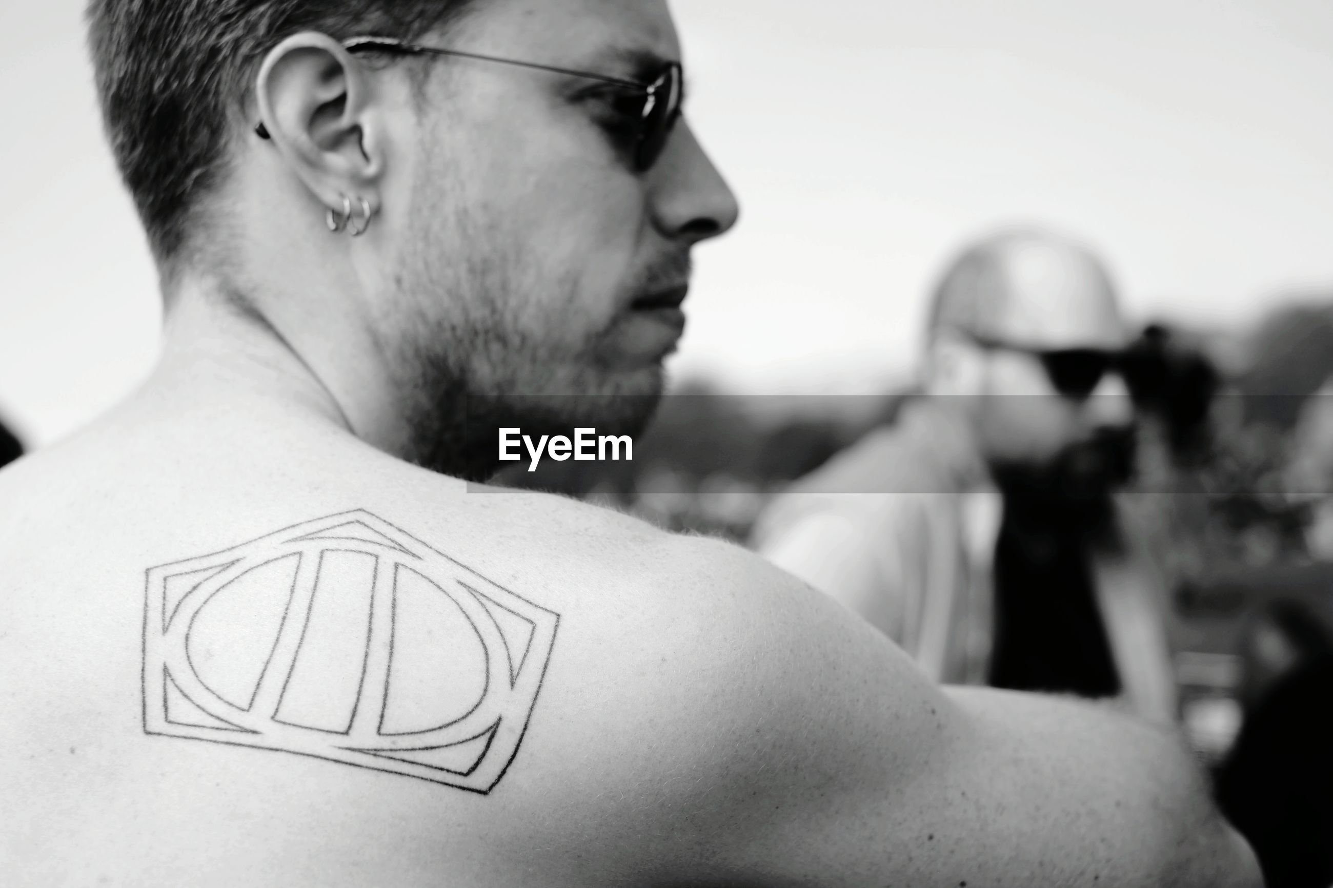 Close-up of shirtless man with tattoo on back