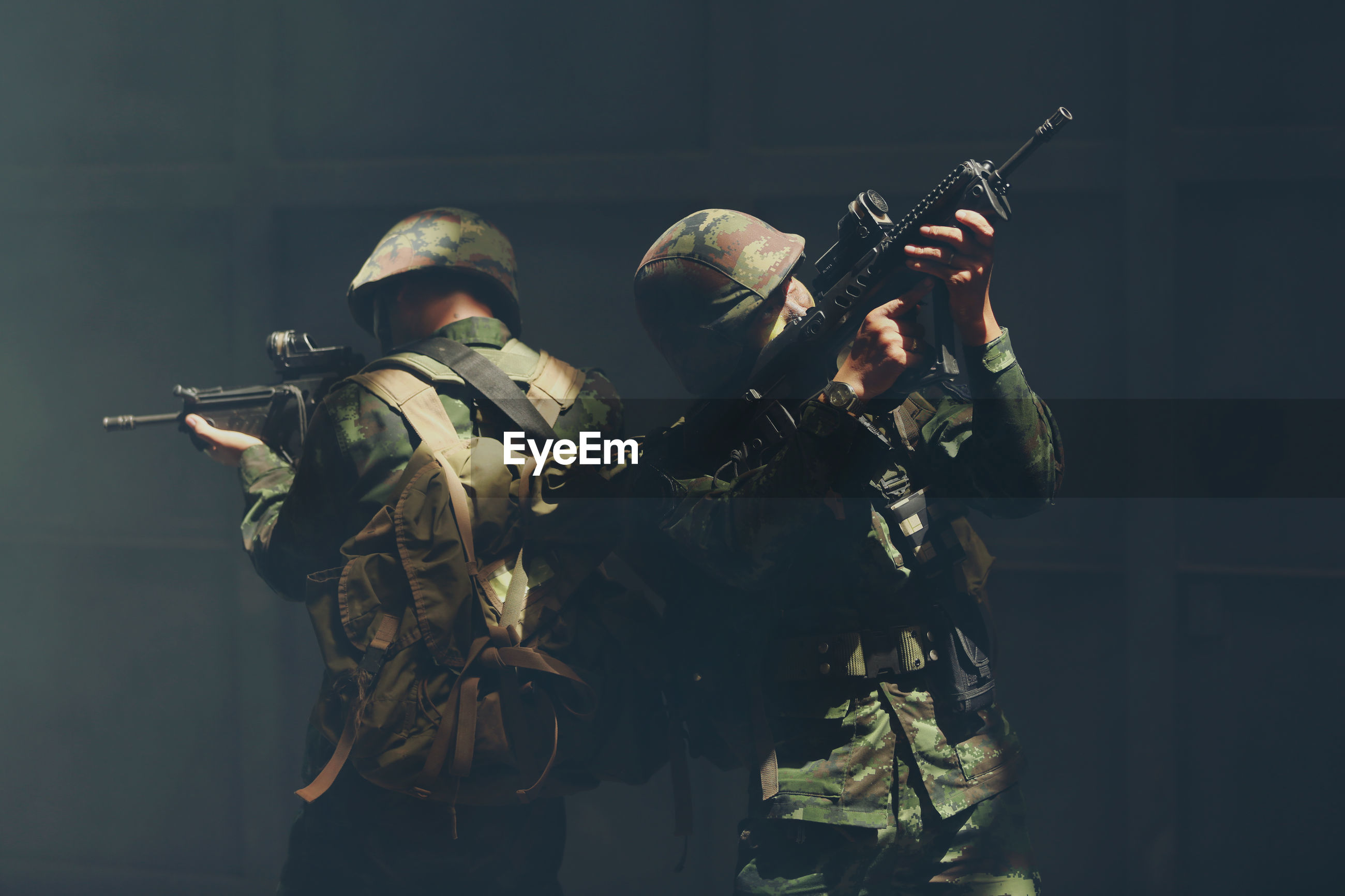 Close-up of soldiers with gun against black background
