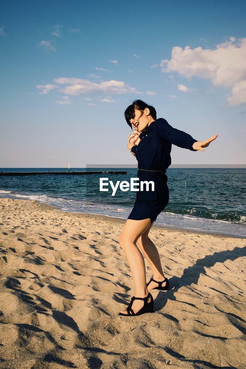 Full Length Of Happy Woman At Beach Against Sky