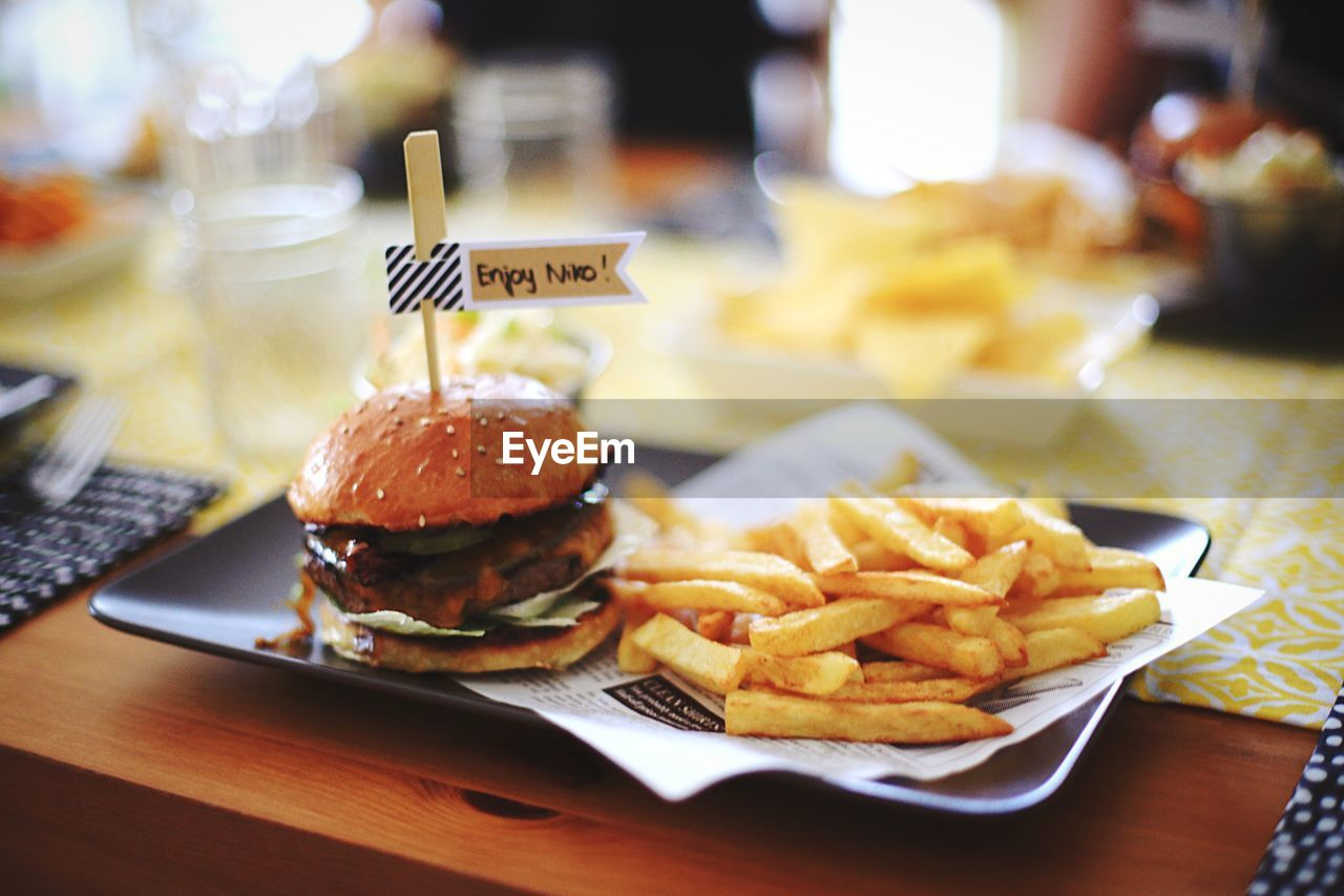 High angle view of french fries and hamburger served on table
