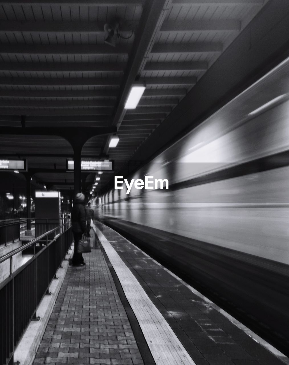 transportation, railroad station, railroad station platform, rail transportation, public transportation, illuminated, real people, indoors, full length, men, one person, travel, blurred motion, motion, mode of transport, women, the way forward, railroad track, lifestyles, standing, subway train, day, people