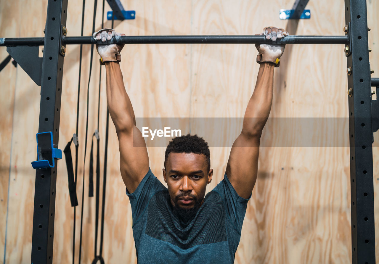 Male athlete hanging from pull-up bar in gym
