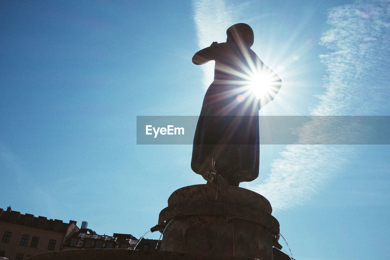 sunbeam, lens flare, sunlight, sun, low angle view, statue, sky, day, blue, outdoors, sculpture, no people, architecture, nature