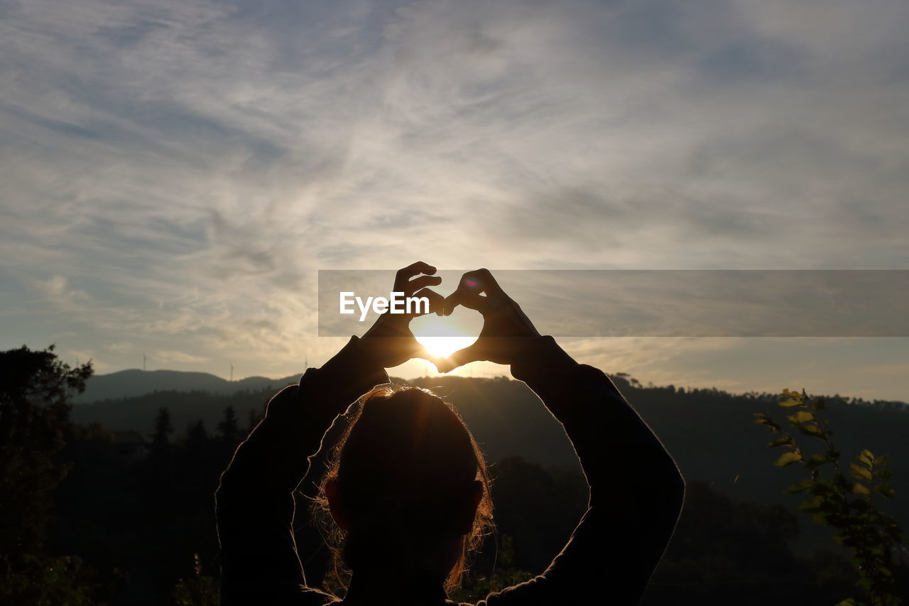 sky, real people, cloud - sky, sunset, one person, leisure activity, lifestyles, nature, beauty in nature, silhouette, heart shape, sunlight, sun, arms raised, making, human arm, men, scenics - nature, positive emotion, outdoors, lens flare, hand