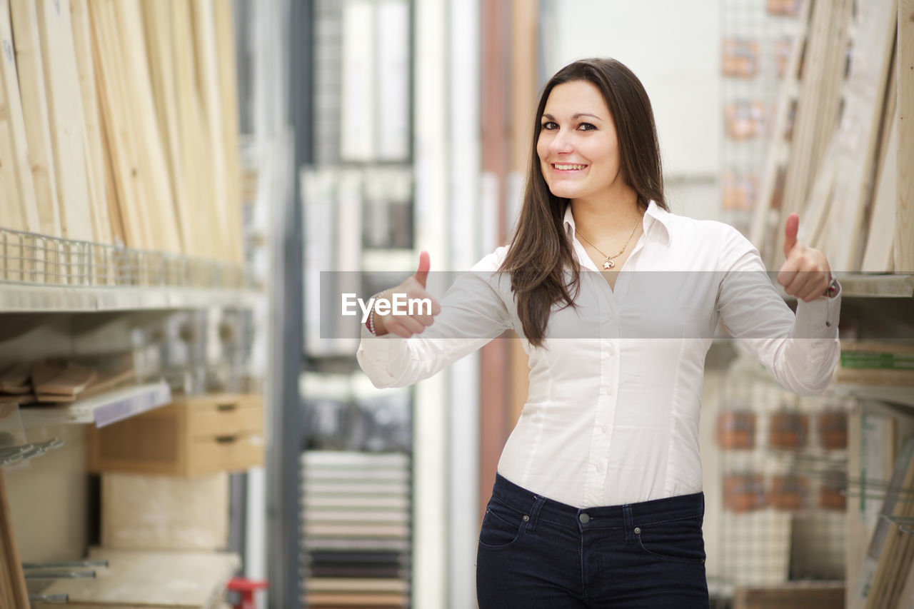 Portrait of smiling young woman showing thumbs up in store