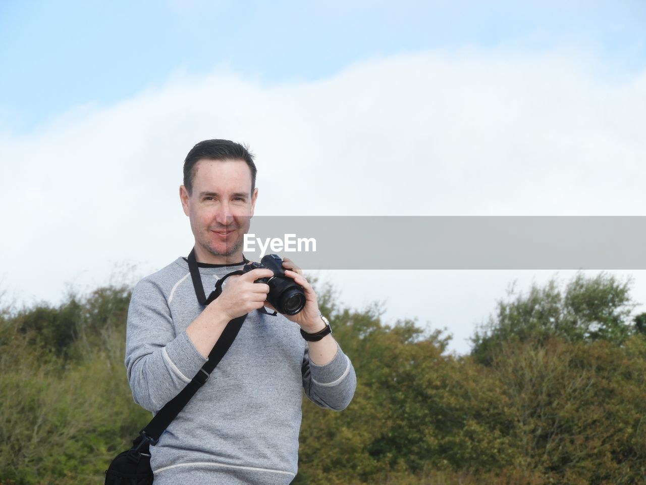 Portrait Of Smiling Man Holding Camera While Standing Against Sky