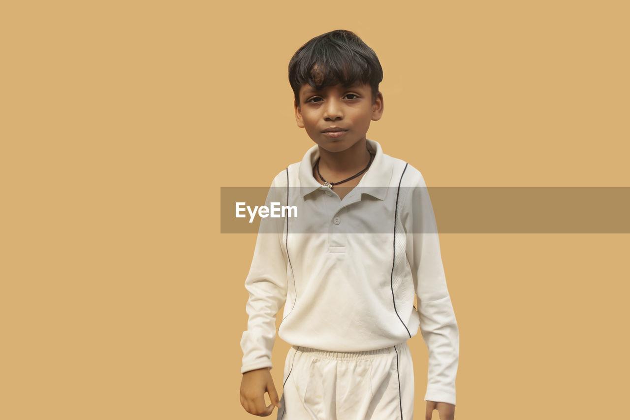 PORTRAIT OF BOY AGAINST ORANGE BACKGROUND