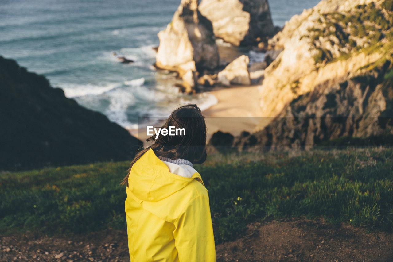 Rear View Of Woman Wearing Yellow Raincoat Looking At Sea