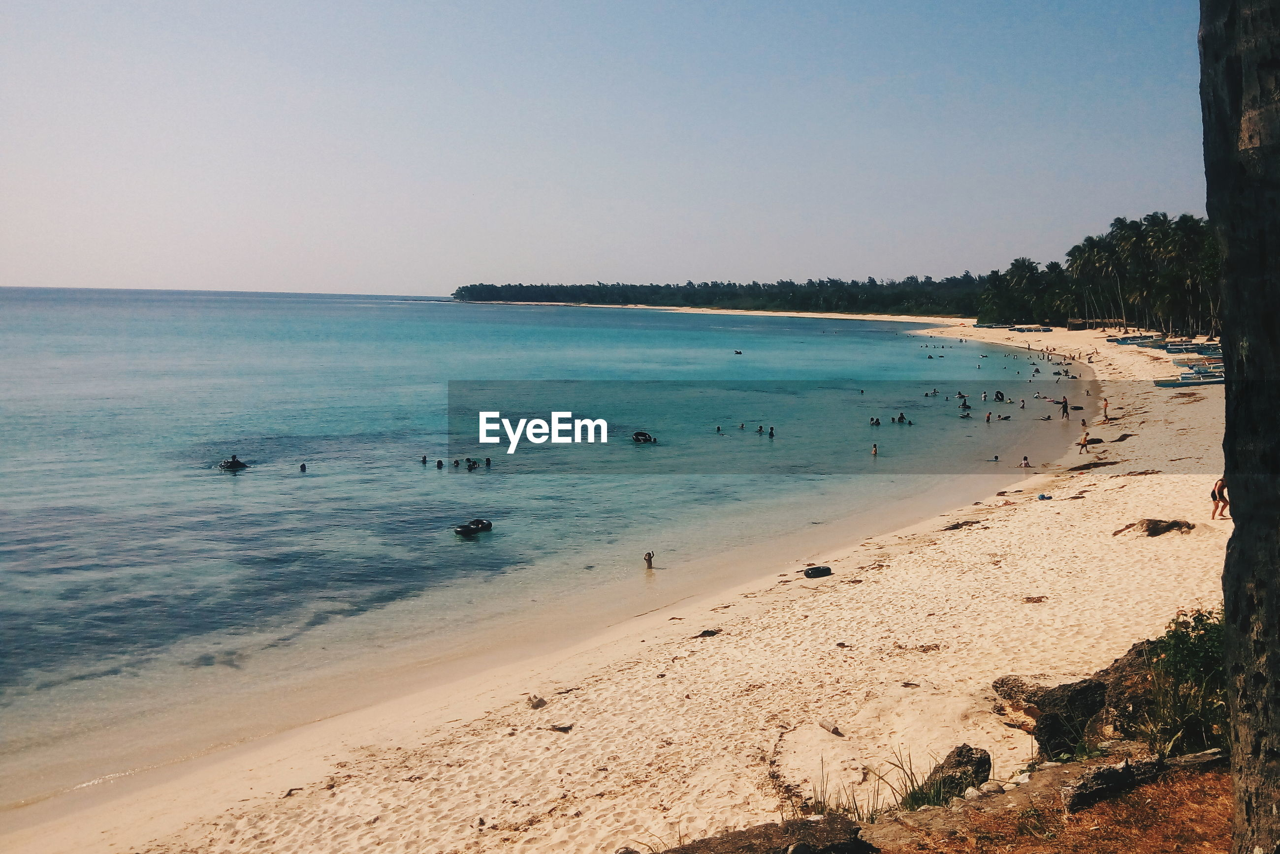 Scenic view of beach against clear sky during sunny day