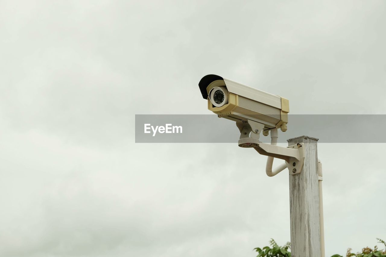 sky, security camera, surveillance, low angle view, cloud - sky, security system, security, no people, protection, safety, technology, day, pole, nature, outdoors, control, watching, photography themes, looking, big brother - orwellian concept, electrical equipment, safety equipment
