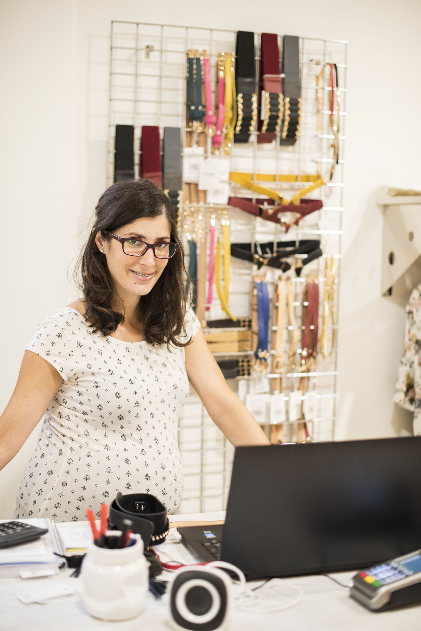 Portrait of pregnant woman using laptop while standing in clothing store