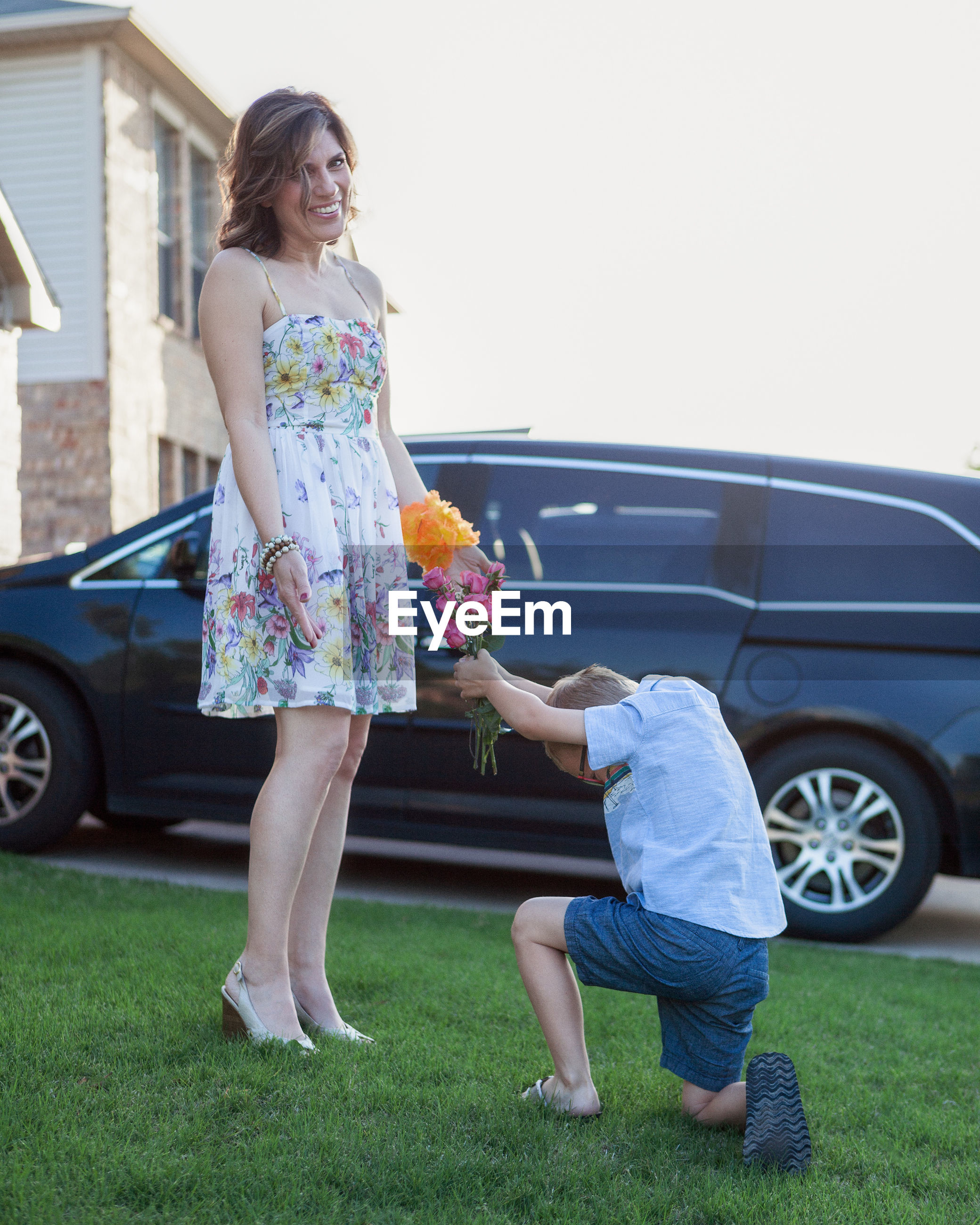 Son proposing mother while kneeling on field against clear sky